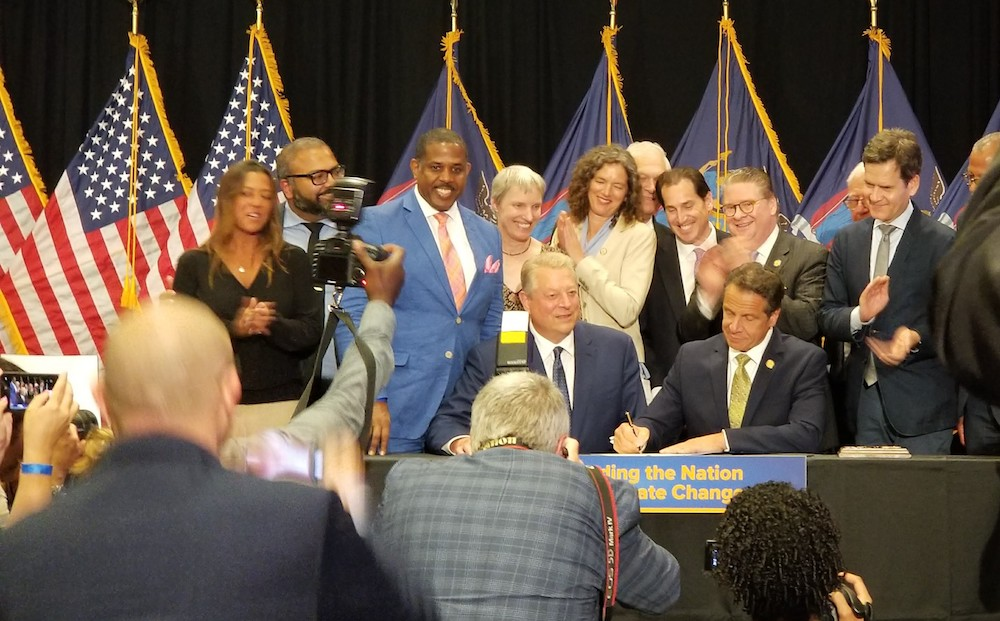 Governor Cuomo signing NY's landmark climate bill with Al Gore and other supporters.