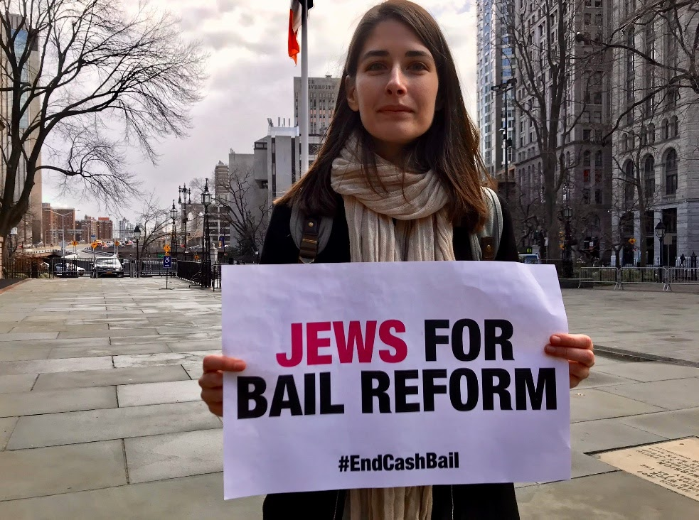 Elena holds sign that says Jews for Bail Reform