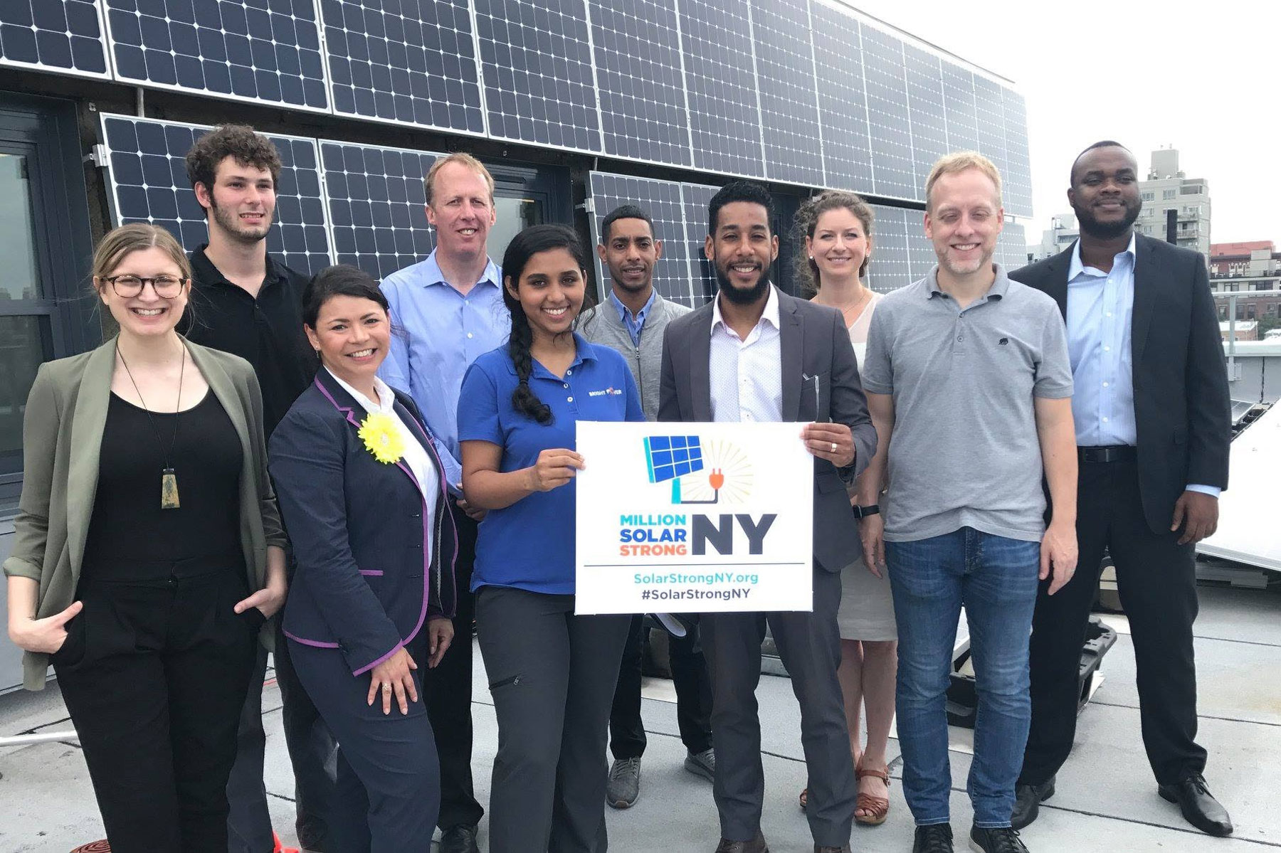 Million Solar Strong NY poses in front of solar panel